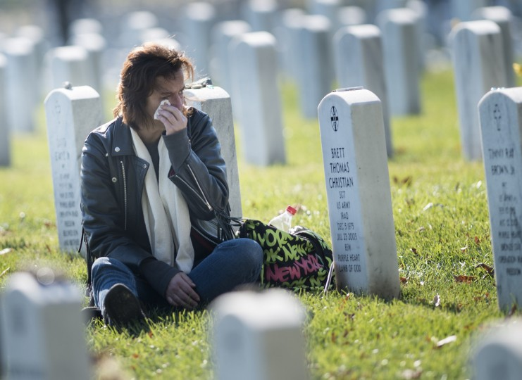 A woman grieves for a soldier buried in Section 60 of Arlington National Cemetery on Veterans' Day, November 11, 2012 in Arlington, Virginia. (Brendan Smialowski/Getty Images)