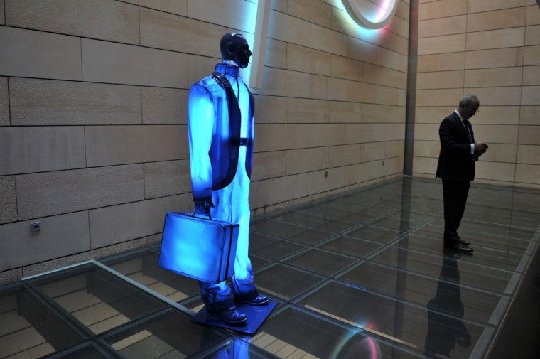 A man looks at his mobile phone by a sculpture of a banker at the National Bank of Greece premises. (Louisa Gouliamaki/Getty Images)