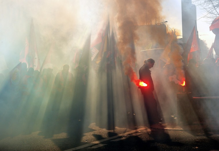A man holds a flare as thousands of people from France and Belgium demonstrate during an anti-austerity protest in Lille. Trade unions lead nationwide strikes and anti-austerity protests across Europe today. (Philippe Huguen/Getty Images)