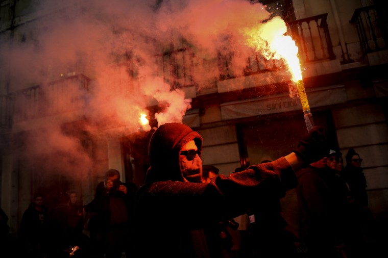 A protester holds a flare during a demonstration in Lisbon during a general strike . General strikes in Spain and Portugal will spearhead the day of action called by European unions and joined by activists as anger over governments' tight-fisted policies boils over. (Patricia De Melo Moreira/Getty Images)