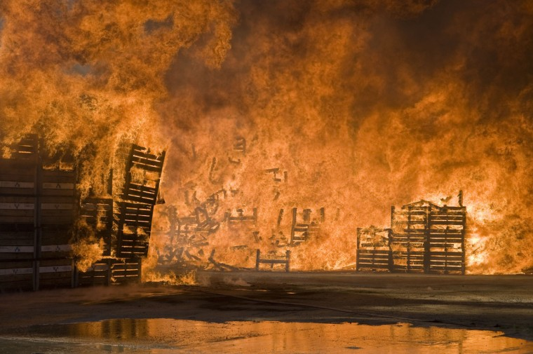 """Fruit bins burn at a packing store in Wolesley, about 120Km North of Cape Town, South Africa. The fire, which burnt more than 15000 wooden bins is thought to be connected to the farmworkers strike. South African police on Wednesday said one person was killed and five others injured as protests by farm workers demanding higher pay descended into violence, prompting calls for the military to be deployed. A week-long protest by farm workers spilled over into bloodshed with chilling echoes of recent mining unrest that has claimed more than 50 lives. """"We can confirm the death of a 28-year-old man in Wolseley and five others wounded,"""" Lybey Swartz of the Western Cape police told AFP. (Rodger Bosch/Getty Images)"""