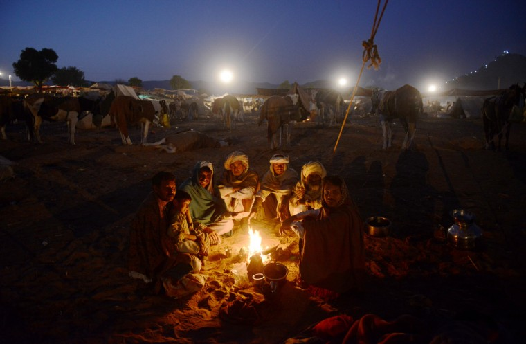 A group of camel traders sit around a fire in the early morning hours at the camel fair grounds on the outskirts of Pushkar . The annual five-day camel and livestock fair, held in the town of Pushkar in the state of Rajasthan is one of the world's largest camel fairs, and apart from buying and selling of livestock it has become an important tourist attraction. (Roberto Schmidt/Getty Images)