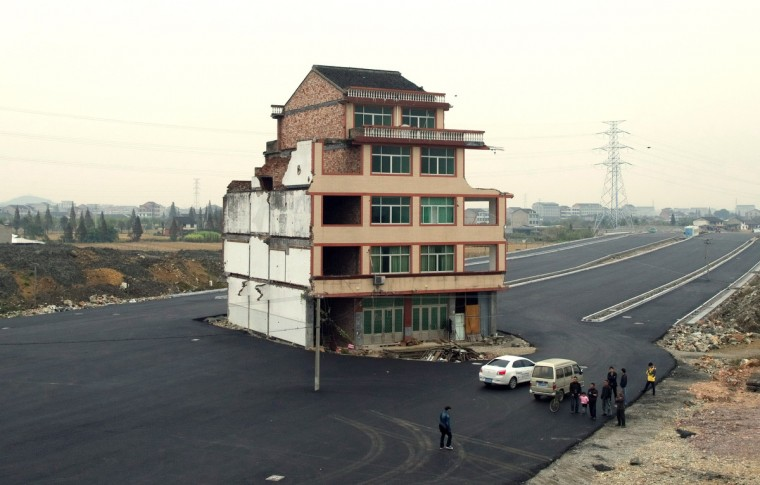 "A half-demolished apartment building standing in the middle of a newly-built road thanks to a Chinese couple that refused to move in Wenling, in eastern China's Zhejiang province. Luo Baogen, 67, and his 65-year-old wife have waged a four-year battle to receive more than the 41,300 USD compensation offered by the local government of Daxi, a Chinese newspaper said. The phenomenon is called a ""nail house"" in China, as such buildings stick out and are difficult to remove, like a stubborn nail. (Getty Images)A half-demolished apartment building standing in the middle of a newly-built road thanks to a Chinese couple that refused to move in Wenling, in eastern China's Zhejiang province. Luo Baogen, 67, and his 65-year-old wife have waged a four-year battle to receive more than the 41,300 USD compensation offered by the local government of Daxi, a Chinese newspaper said. The phenomenon is called a ""nail house"" in China, as such buildings stick out and are difficult to remove, like a stubborn nail. (Getty Images)standing"