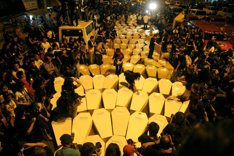 "Philippine journalists and students carry mock coffins as they march towards Malacanang Palace in Manila to commemorate the third anniversary of the November 23 Maguindanao massacre. Dozens of members of a clan whose leaders are on trial for the Philippines' worst political massacre are candidates in 2013 elections, some for the president's party, media and rights groups said November 23. The revelations sparked outrage on the three-year anniversary of the massacre, in which 58 people died, with critics saying the Ampatuan family's enduring political influence underlined the country's ""culture of impunity."" (Noel Celis/Getty Images)"