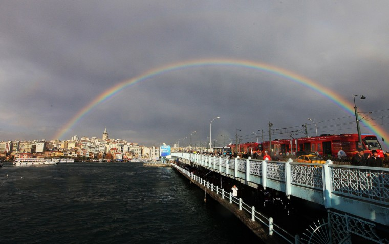 A rainbow is seen over the Galata bridge and Galata Tower after a rainy day in Istanbul. (Mira/Getty Images)