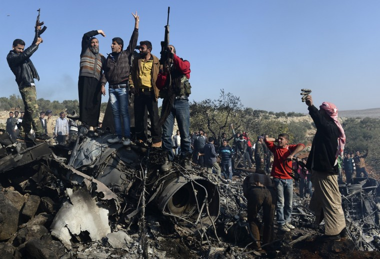 Syrian rebels celebrate on top of the remains of a Syrian government fighter jet which was shot down at Daret Ezza, on the border between the provinces of Idlib and Aleppo. Syrian rebels captured a pilot manning the fighter jet downed over Daret Ezza in the northern province of Aleppo, witnesses told an AFP reporter in the town. (Francisco Leong/Getty Images)