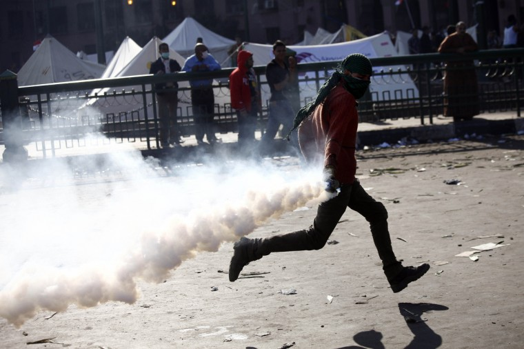 A protester throws back a tear gas canister during clashes with Egyptian riot Police on Tahrir Square in Cairo. Police fired tear gas into Cairo's Tahrir Square, where several hundred protesters spent the night after a mass rally to denounce President Mohamed Morsi's assumption of expanded powers. (Mahmoud Khaled/Getty Images)