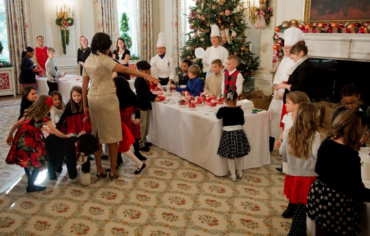 First Lady Michelle Obama (C) holds the presidential dog Bo on his leash as young children run in to pet him during the first viewing of the White House 2012 holiday decorations in Washington, DC. (Jim Watson/Getty Images)