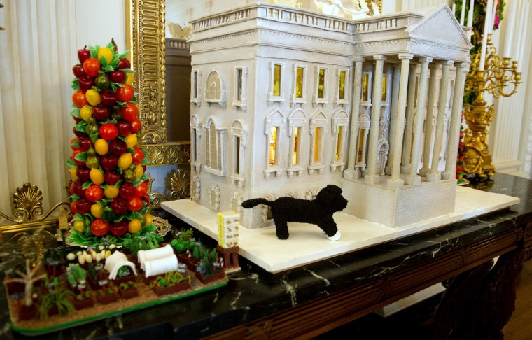 A gingerbread White House and decorations hang in the State Dining Room during the first viewing of the White House 2012 holiday decorations in Washington, DC. (Jim Watson/Getty Images)