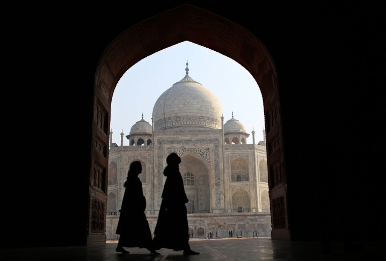 Indian tourists walk past an archway at the historic Taj Mahal in Agra . A highway, that opened up in August 2012, connecting India's Taj Mahal tourism town of Agra with the capital New Delhi has slashed driving time by more than half. The 165-kilometre (100-mile) Yamuna Expressway promises a two-hour drive through the crowded towns of Uttar Pradesh state to Agra, where the Taj Mahal draws almost three million domestic and foreign tourists a year. (Andrew Caballero-Reynolds/Getty Images)