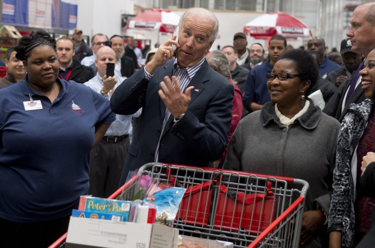 US Vice President Joe Biden talks on an employee's cellphone during a visit to a Costco store on a shopping trip in Washington, DC. Biden made the visit to the first Costco store located in Washington, DC, during its grand opening. (Saul Loeb/Getty Images)