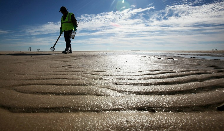 December 6, 2010 - A worker cleans tarballs from the BP oil spill in Waveland, Miss. Nearly eight months after the spill, tarballs continued to washing up on the beach. (Photo by Mario Tama/Getty Images)