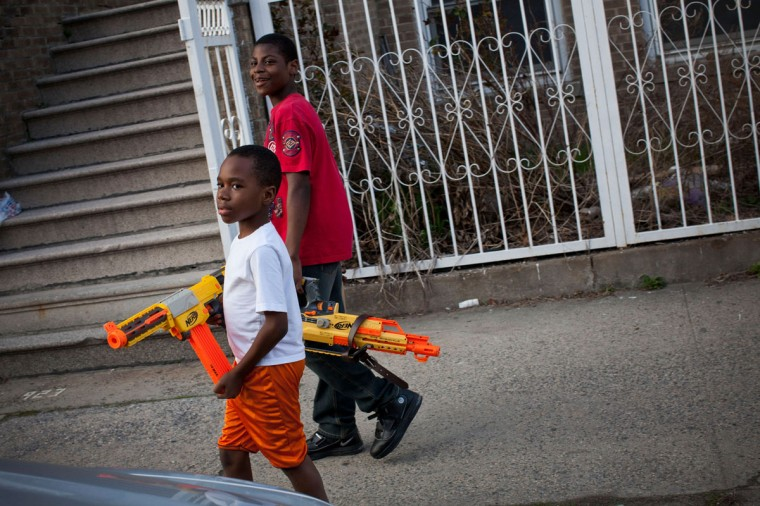 March 22, 2012: Children playing with toy guns walk past a vigil for Ramarley Graham in the Bronx borough New York City. Graham, 18, was shot in the chest by police officers in his grandmother's bathroom after the officers entered the house without a warrent. Graham, was unarmed; he was attempting to flush a bag of marijuana down the toilet. (Andrew Burton/Getty Images)