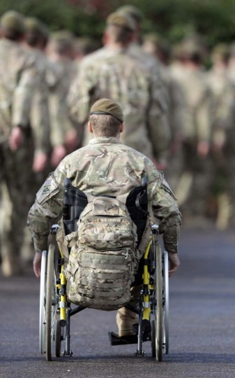 An injured serviceman follows as soldiers from 1st Battalion The Royal Anglian Regiment (The Vikings) march from the parade ground after they received their Afghanistan Operational Service Medals at Picton Barracks in Bulford, England. The parade was the first in a series of events marking the end of their successful six-month deployment to Afghanistan as part of Task Force Helmand. (Matt Cardy/Getty Images)