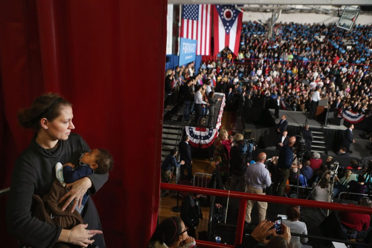"A woman cradles her infant as she listens to U.S. President Barack Obama at a campaign rally at Mentor High School in Mentor, Ohio. With just three days left until the presidential election, Obama and his opponent, former Massachusetts governor Mitt Romney, are hopping from one ""swing state"" to the next in a last-minute rush to persuade undecided voters. (Chip Somodevilla/Getty Images)"