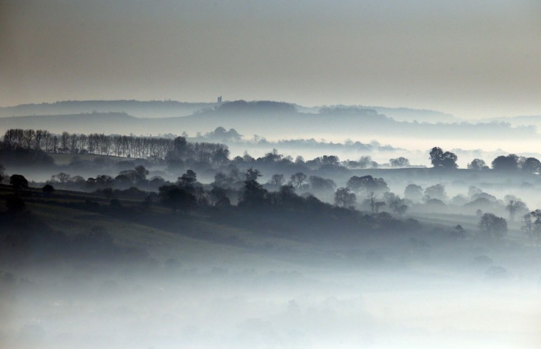 Mist lingers in fields viewed from Glastonbury Tor as the sun rises over the Somerset countryside in Glastonbury, England. Parts of the UK have experienced one of the coldest starts to November for many years and the Met Office is predicting that the coming winter could be a colder one than average. (Matt Cardy/Getty Images)