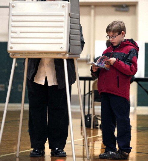 STERLING HEIGHTS, MI: A young boy reads a book while his parent votes in the U.S. presidential election at Carleton Middle School November 6, 2012 in Sterling Heights, Michigan. Recent polls show that U.S. President Barack Obama and Republican presidential candidate Mitt Romney are in a tight race. (Bill Pugliano/Getty Images)