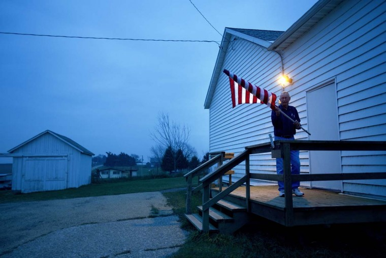 GEORGETOWN, WI: Election Inspector Jim Nodorft unfurls the American flag to hang it up outside the Smelser Town hall as the polls opened at 7 a.m. on November 6, 2012 in Georgetown, Wisconsin. U.S. citizens go to the polls today to vote in the election between Democratic President Barack Obama and Republican nominee former Massachusetts Gov. Mitt Romney. (Mark Hirsch/Getty Images)