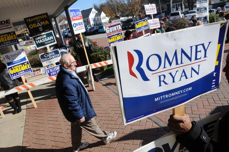 MANCHESTER, NH: Voters walk past supporters holding signs after casting ballots at Northwest Elementary School November 6, 2012 in Manchester, New Hampshire. The race between incumbent President Barack Obama and Republican challenger Mitt Romney will come down to certain swing states like New Hampshire. (Darren McCollester/Getty Images)