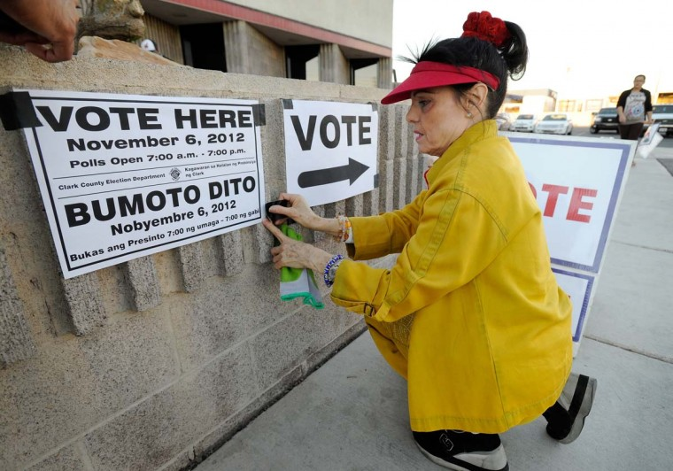 LAS VEGAS, NV: Election worker Susan Keller sets up directional signs before the polling station at the Clark County Fire Training Center opens on November 6, 2012 in Las Vegas, Nevada. Voting is underway in the battleground state of Nevada as President Barack Obama and Republican nominee former Massachusetts Gov. Mitt Romney remain in a virtual tie in the national polls. (David Becker/Getty Images)