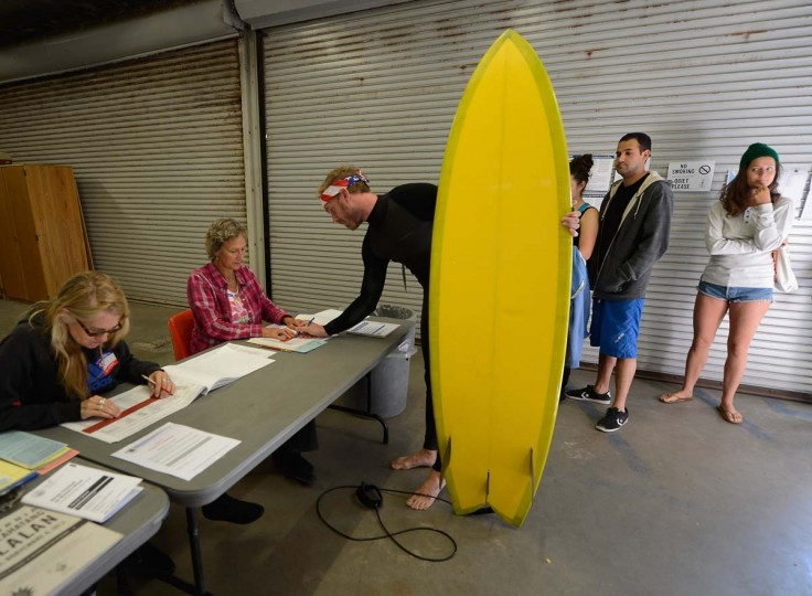 "LOS ANGELES, CA: Mike Wigart (2nd L), 30, picks up his ballot at a polling station in the garage of the Los Angeles County lifeguard headquarters on November 6, 2012 in Los Angeles, California. Californians will cast ballots in dozens of tight races including Gov. Jerry Brown's tax plan, abolishing the death penalty, easing the state's strict ""three strikes"" sentencing law and also in the Presidential race between Democratic President Barack Obama and Republican candidate Mitt Romney. (Kevork Djansezian/Getty Images)"