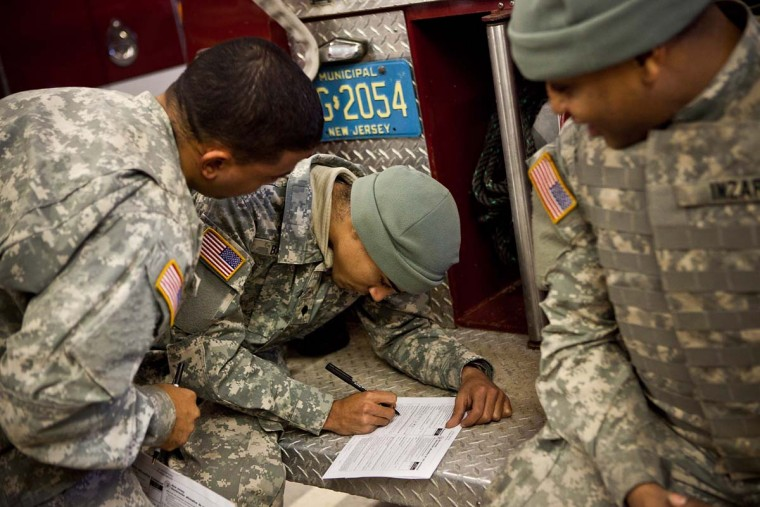BAY HEAD, NJ: Members of the Army National Guard fill out absentee voter ballots for the presidential election while temporarily stationed along the New Jersey coastline to help with Superstorm Sandy clean up on November 6, 2012 in Bay Head, New Jersey. As the New Jersey coastline continues to recover from Superstorm Sandy, numerous polling stations have had to be merged and relocated due to storm damage and power outages. (Andrew Burton/Getty Images)