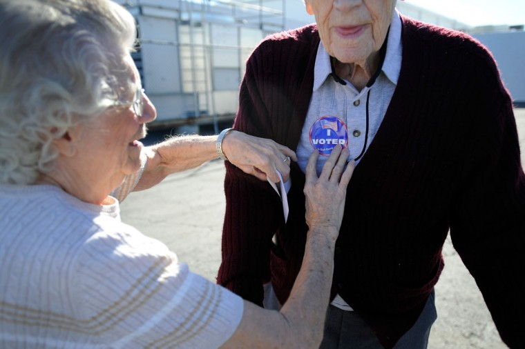 "Pauline Vallee, left, helps Robert Krack with his ""I Voted"" sticker after he cast his ballot at the polling station at John Fremont Middle School in Las Vegas, Nevada. Krack, 91, has voted in every presidential election since Franklin D. Roosevelt (David Becker/Getty Images)"