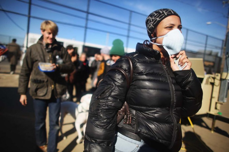 NEW YORK, NY: Rockaway resident Saajida O'Quinn wears a protective mask as she prepares to vote in a makeshift tent set up as a polling place at Scholars' Academy, PS 180, in the Rockaway neighborhood on November 6, 2012 in the Queens borough of New York City. The Rockaway section of Queens was one of the hardest hit areas and O'Quinn's home was damaged in Superstorm Sandy. Many voters in New York and New Jersey are voting at alternate locations in the presidential election due to disruption from the storm. (Mario Tama/Getty Images)