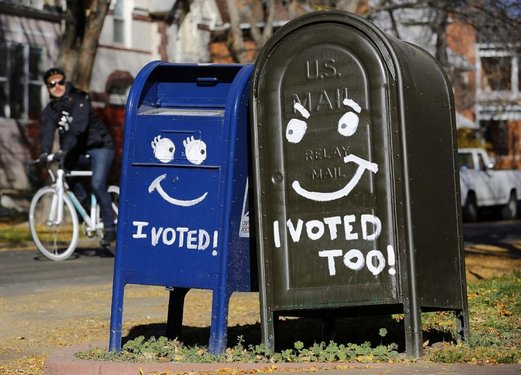 DENVER, CO: A biker passes by a pair of mailboxes in the Capitol Hill neighborhood November 6, 2012 in Denver, Colorado. Colorado is considered by most experts to be one of the key battleground state in this year's presidential election. (Marc Piscotty/Getty Images)