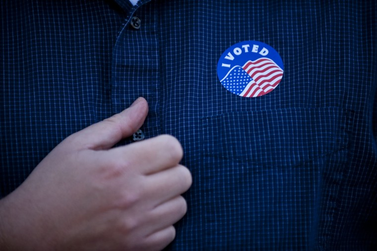 "Rev. Chase Peeples proudly displays his ""I Voted"" sticker at the Country Club Congregational Church in Kansas City, Missouri. Rev. Chase voted earlier near his home, but stopped by his church to experience his first election as new pastor. (Photo by Julie Denesha/Getty Images)"