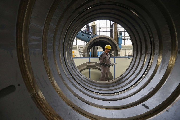 A worker, at the photographer's request, walks past the casing of a gas turbine at the Siemens gas turbine plant on November 11, 2012 in Berlin, Germany. Earlier in the Siemens announced plans to save EUR 6 billion by 2014 in order to strengthen its competiveness. (Sean Gallup/Getty Images)
