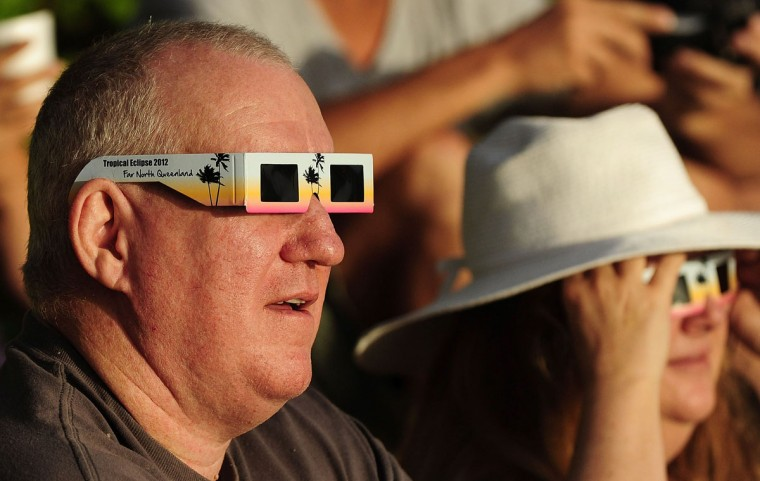 A spectator views the solar eclipse through special eclipse viewing glasses on November 14, 2012 in Palm Cove, Australia. (Ian Hitchcock/Getty Images)