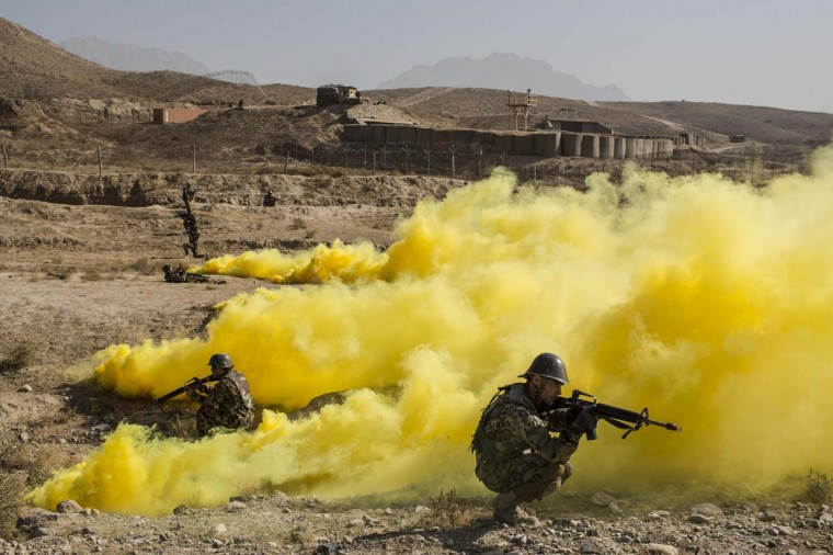 Afghan National Army cadets secure the perimeter as smoke bombs, simulating detonated IED's cover the area during a Taliban capture military exercise, overseen by French and Canadian soldiers, at the Kabul Military Training Center (KMTC)d in Kabul, Afghanistan. (Daniel Berehulak/Getty Images)
