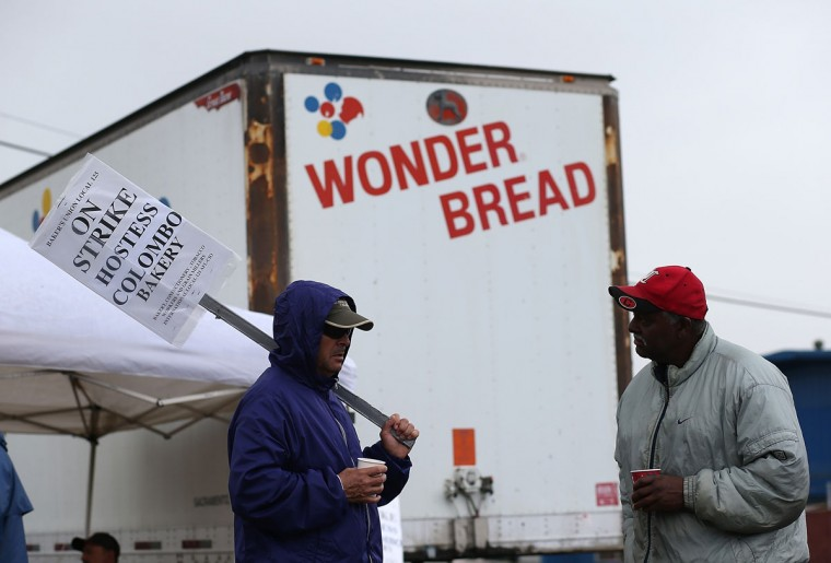 Striking bakery workers stand near a truck outside of the Interstate Bakeries facility in Oakland, Calif., on Nov. 16,2 012. Hostess Brands, the maker of Twinkies, Ding Dongs and Wonder Bread, announced plans to liquidate its assets and lay off nearly 18,500 employees due to a workers' strike brought on by an imposed contract that would cut workers' wages by 8 percent. (Justin Sullivan/Getty Images)