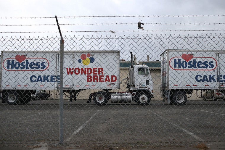 Trucks sit idle at the Hostess baking facility in Oakland, Calif. Hostess Brands, the maker of Twinkies, Ding Dongs and Wonder Bread, announced plans to liquidate its assets and lay off nearly 18,500 employees due to a workers' strike brought on by an imposed contract that would cut workers' wages by 8 percent. (Justin Sullivan/Getty Images)