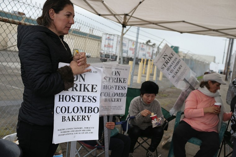 Striking bakery workers stand near a truck outside of the Hostess baking facility in Oakland, California. Hostess Brands, the maker of Twinkies, Ding Dongs and Wonder Bread, announced plans to liquidate its assets and lay off nearly 18,500 employees due to a workers' strike brought on by an imposed contract that would cut workers' wages by 8 percent. (Justin Sullivan/Getty Images)