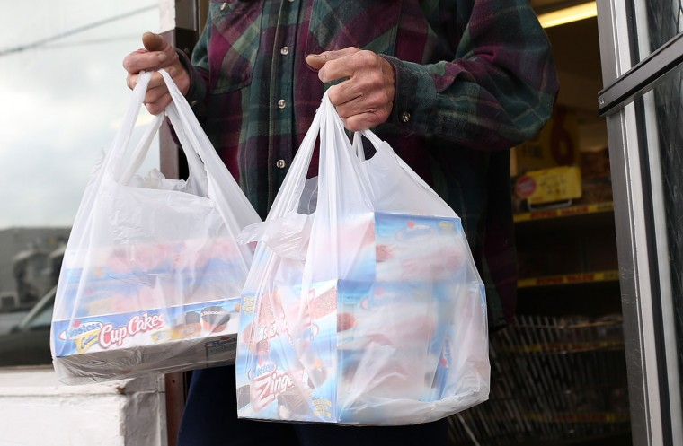 A customer carries bags of Hostess products at a Wonder Hostess Bakery Outlet in San Leandro, Calif. Hostess Brands, the maker of Twinkies, Ding Dongs and Wonder Bread, announced plans to liquidate assets, prompting some concerned shoppers to stock up on the company's products. (Justin Sullivan/Getty Images)