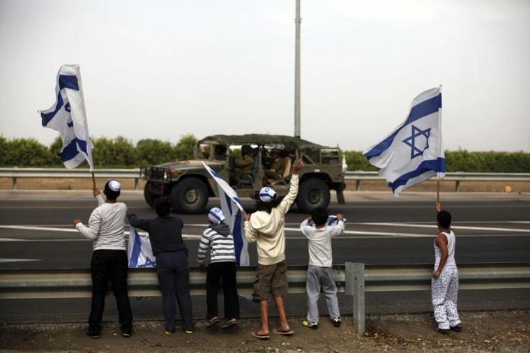 NOVEMBER 17 — Israeli children wave their national flag as they greet an army convoy passing on a road leading to the Israel-Gaza border near the southern Israeli town of Ofakim on November 17, 2012 in Israel. (Lior Mizrahi/Getty Images)