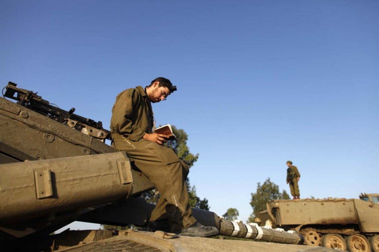 NOVEMBER 18 — Israeli soldiers do their morning prayers in a deployment area on Israel's border with the Gaza Strip, on November 18, 2012 in Israel. Israeli shelling of Gaza has entered its fifth day, with two media buildings being recently struck and several journalists injured. (Lior Mizrahi/Getty Images)