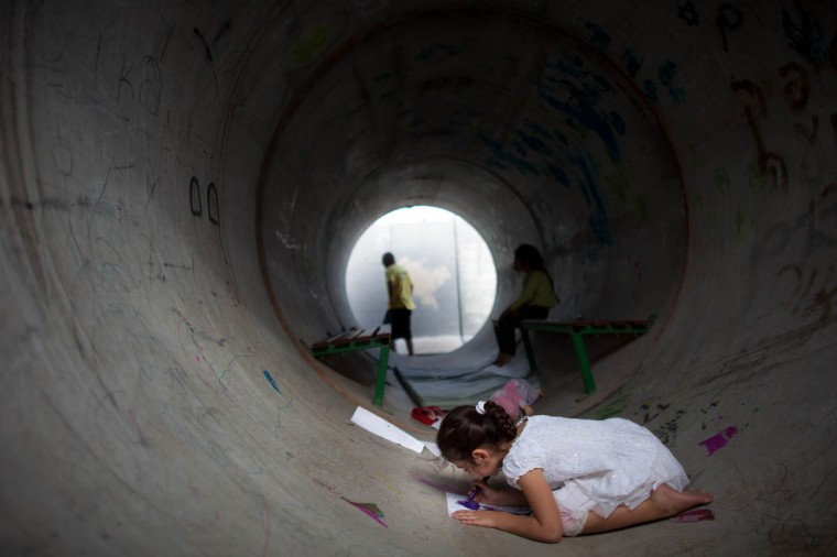 An Israeli child plays in a large concrete pipe used as a bomb shelter in Nitzan, Israel. According to reports at least 90 Palestinians have been killed and more than 700 wounded during the Israeli offensive in the Gaza Strip. (Uriel Sinai/Getty Images)