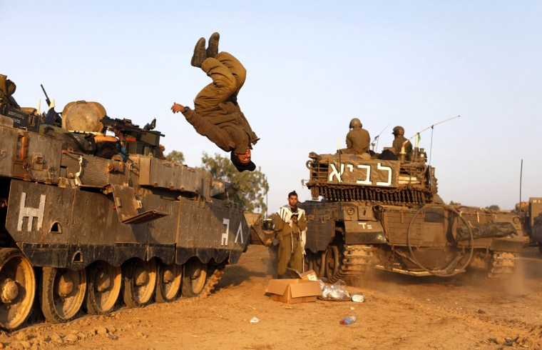 NOVEMBER 20: An Israeli soldier jumps from a tank in a deployment area as the conflict between Palestine and Gaza enters its seventh day on Israel's border with the Gaza Strip. (Lior Mizrahi/Getty Images)