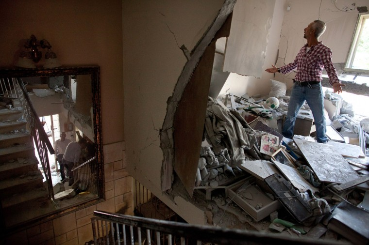 NOVEMBER 20: Aaron Hachmon reacts to the damage caused to his house after it was hit by a rocket fired from the Gaza Strip in Beersheba, Israel. (Uriel Sinai/Getty Images)