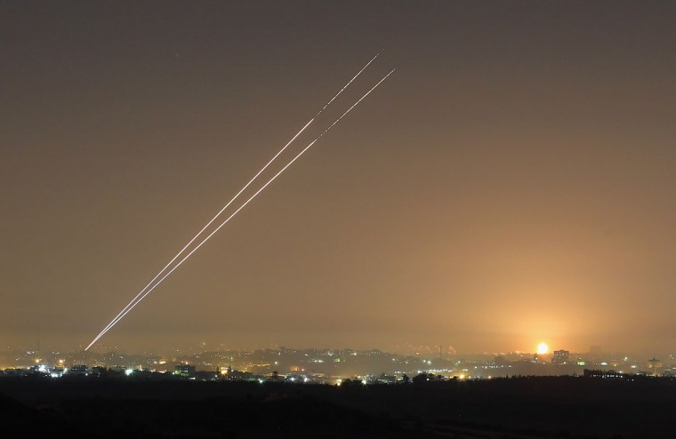 NOVEMBER 21: During the last hour of hostilities, militants launch rockets from Gaza City as an Israeli bomb explodes on the horizon on Israel's border with the Gaza Strip. (Christopher Furlong/Getty Images)