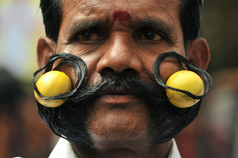 Indian Hindu devotee of goddess Mahankali, M.Ramadass holds two limes in his seven ft. moustache as he poses during a Swarnalatha Rangam ceremony at The Sri Ujjaini Mahakali Temple in Secunderabad, the twin city of Hyderabad, on July 18, 2011. Swarnalatha Rangam is a ritual where it is believed that the goddess Mahankali enters the body of an unmarried woman and predicts the future. (Noah Seelam/AFP/Getty Images)