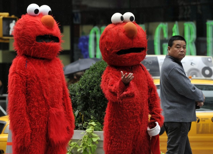 Two people, dressed in knockoff Elmo costumes, wait to pose for pictures with tourists in Times Square in October 2012. The number of costumed Muppets in New York got more attention after Republican presidential candidate Mitt Romney mentioned Sesame Street in a debate. (Timothy A. Clary/AFP/Getty Images)