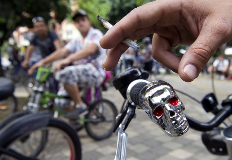 October 6, 2012: A man smokes marijuana as he rides his bike during the first world bicycle ride against drug trafficking and in favour of the legalization of self-cultivation of marijuana for medicinal and recreational purposes in Medellin, Antioquia department, Colombia. (Raul Arboleda/AFP/Getty Images)