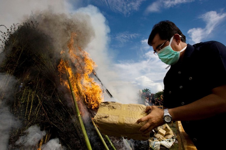 October 17, 2012: A police official sets fire to a package containing marijuana as hundreds of bundles of the drug go up in flames in Banda Aceh. (Chaideer Mahyuddin/AFP/Getty Images)