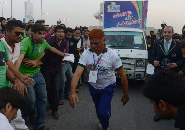 Saddi Muhammad achieves a record for using his mustache to pull a 1.7 tonne pickup truck a distance of 60.3 metres at the week-long youth festival in the eastern city of Lahore on October 21, 2012. Pakistan may not have brought home any medals from this summer's Olympics, but it can now lay claim to world records in chapati-making, plug-wiring and chessboard-arranging. (Arif ALIArif Ali/AFP/Getty Images)