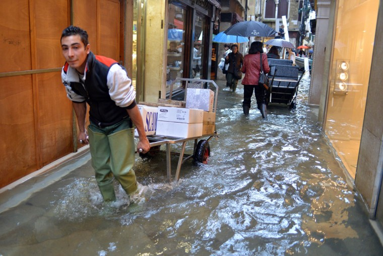 "An employee pulls a trolley with goods in a small street during an ""acqua alta"" (literally, ""high water"") on Oct. 27, 2012 in Venice. Caused by a convergence of high tides and a strong sirocco wind, the ""acqua alta"", reached 127 centimeters, or 50 inches, in the morning. (Andrea Pattaro/AFP/Getty Images)"