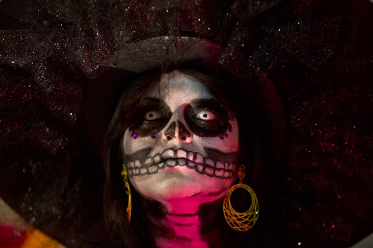 A woman dressed up as the death poses on October 31, 2012 in Mexico city, during preparations on the eve of the Day of the Dead celebrations. (Ronaldo Schemidt/AFP/Getty Images)
